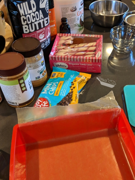 A photograph of all of the ingredients needed to make this paleo vegan peppermint fudge. Wild Foods brand cocoa butter wafers, cashew butter, organic candy canes, Enjoy Life bran mini chocolate chips, as well as a parchment-lined red silicone square pan and several small bowls for measuring and mixing. The edge of a teal food scale is peaking in on the right side.