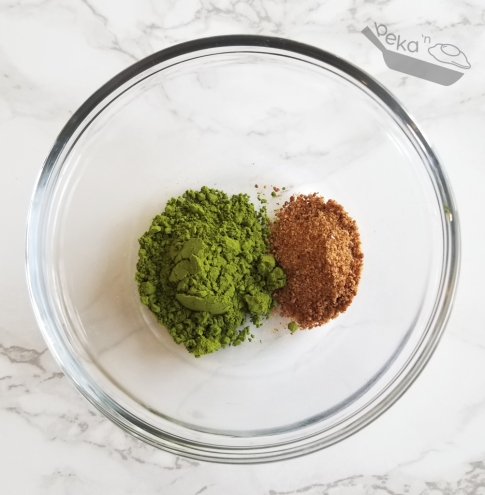An overhead shot of matcha powder and coconut sugar in a small clear glass bowl on a white marble background.