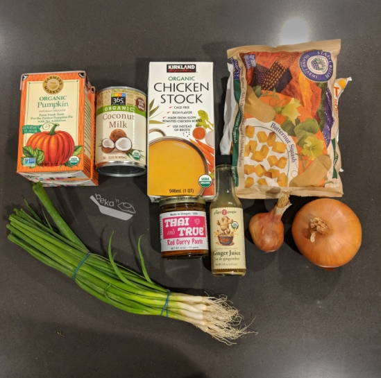 An overhead photo of the ingredients needed to make the soup on a dark gray quartz countertop background. Two stacked cartons of organic pumpkin puree, a can of coconut milk, a carton of chicken stock, two stacked brown bags - one of frozen butternut squash and one of cauliflower underneath (the bag of frozen cauliflower is not really visible in the image), a jar of Thai & True red curry paste (my absolute favorite), a small bottle of ginger juice, one shallot, one yellow onion, and a handful of scallions with two blue rubber bands keeping the bunch together.