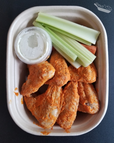 Overhead shot of Stella's Kitchen buffalo wings meal in a light brown carton on a black background.