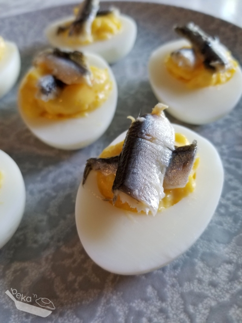 A close up shot of four deviled eggs with pieces of white anchovy on top. On a gray ceramic plate.