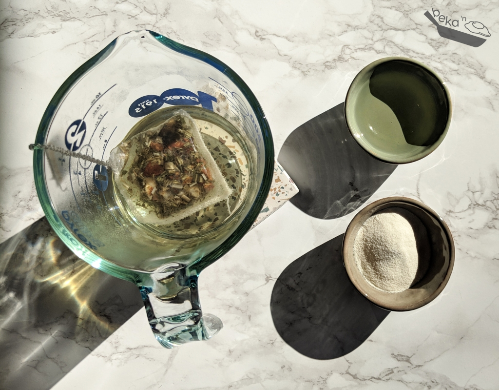 An overhead image of ingredients on a white marble background with shadows on the lower left due to natural lights. A 2cup clear glass measuring cup with tea in a tea bag on a speckled stone coaster, a small green clay bowl with a clear liquid (white grape juice) and a small beige clay bowl with a white powder (collagen).