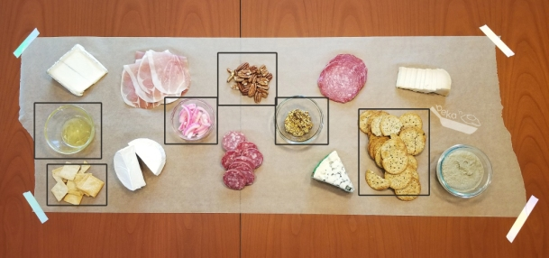 An overhead shot of the party platter with black squares around the accoutrements indicating placement for how to build your platter. Items include homemade mustard, homemade pickled onions, crackers, pecans, and a small bowl of honey.