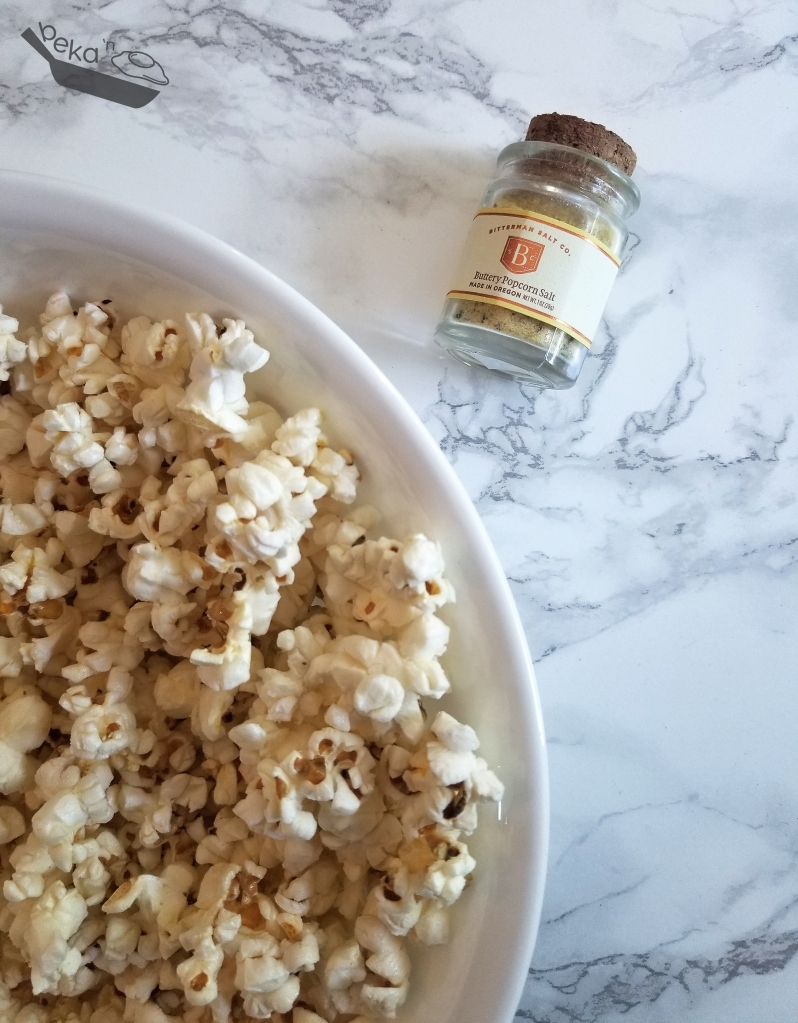 An overhead shot of popcorn in a large white bowl in the left bottom 2/3 of the image. The bowl is on a white marble background. In the top right there is a small clear glass jar with a corked lid. The label reads Buttery Popcorn Salt.