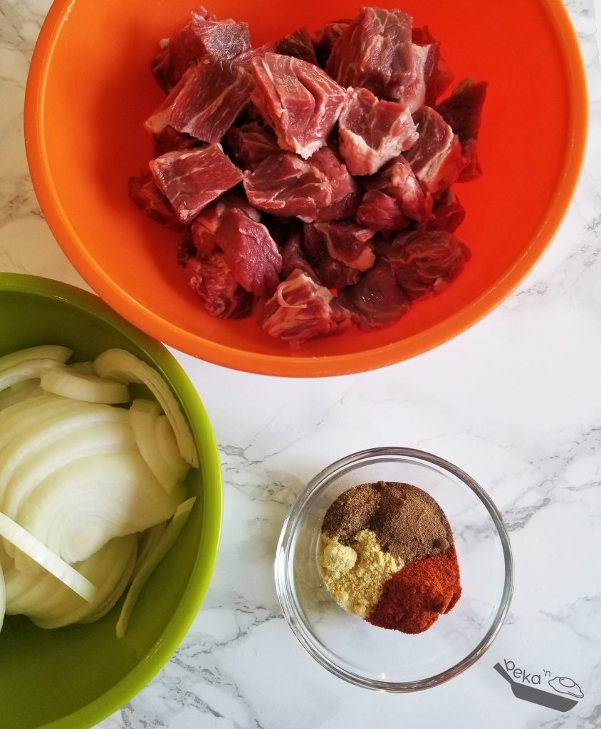 A colorful overhead shot on white marble background of raw ingredients. In the top half of the image, an orange bowl holds cut up beef. In the bottom left there is a green bowl with sliced onions. In the bottom middle/right of the image, there is a small, clear glass bowl with several different spices. It looks very pretty.