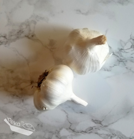 An overhead shot of two full bulbs of garlic on a white marble background.