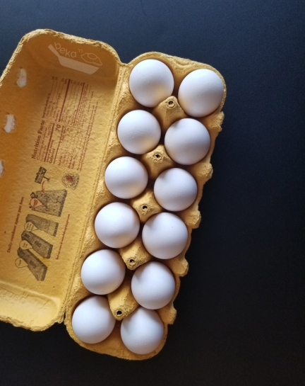 An overhead shot of a dozen white eggs in a yellow carton. The carton sits on a black background.