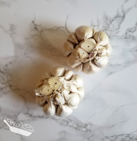 An overhead shot of two bulbs of garlic on a white marble background. The garlic has been peeled of its outermost layers and the top has been cut off revealing the tops of individual garlic cloves within the intact bulb.