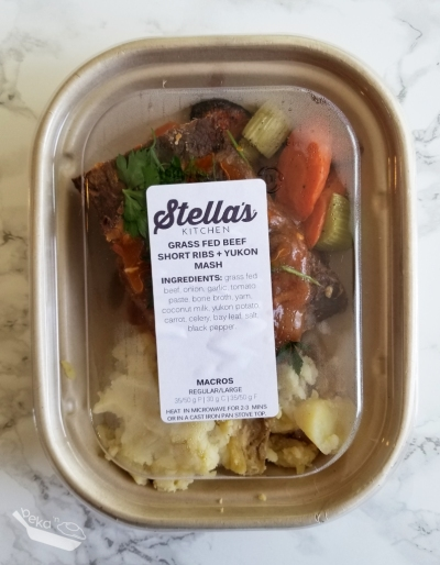 An overhead shot of Stella's Kitchen Grass Fed Beef Short Ribs meal in a light brown carton with clear lid on a white marble background.