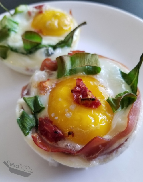 A close up of a Meaty Egg Cup. The foreground shows an egg wrapped in prosciutto with scallions and sun dried tomato pieces. There is a second egg cup in the background, but without meat. The eggs sit on a white plate.