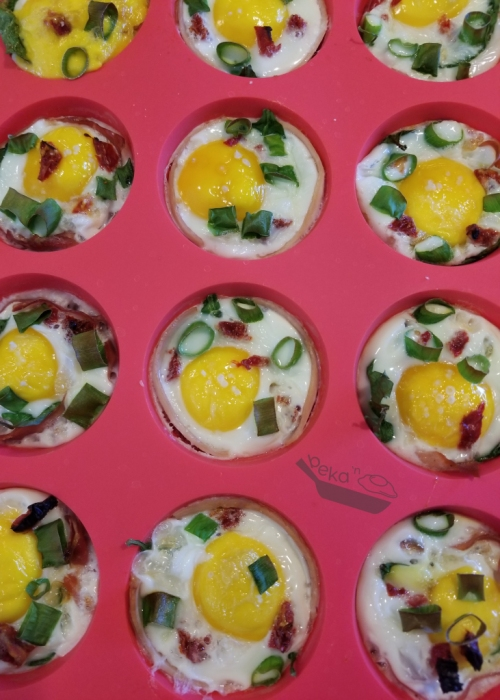 An overhead view of the cooked meaty egg cups. The whites are fully cooked while the yolks still have some life to them. You can see the veggies and meat that were added to each cup.