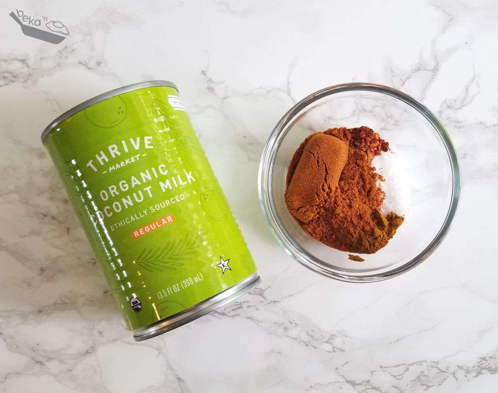 An overhead shot of a green can of Thrive Market Organic Coconut Milk and a small clear glass bowl with red spice powder on a white marble background.